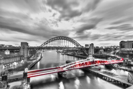 Black white and red swing bridge photograph