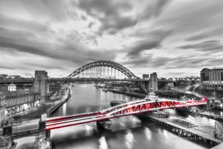 Black white and red swing bridge photograph